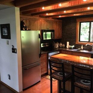 他の地域の小さいおしゃれなキッチン (アンダーカウンターシンク、フラットパネル扉のキャビネット、中間色木目調キャビネット、木材カウンター、グレーのキッチンパネル、石タイルのキッチンパネル、シルバーの調理設備、無垢フローリング) の写真