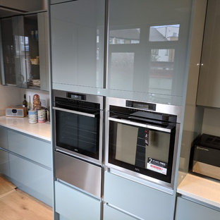 Mid-sized modern u-shaped separate kitchen in London with an undermount sink, flat-panel cabinets, turquoise cabinets, quartzite benchtops, white splashback, stone slab splashback, black appliances, vinyl floors, no island, brown floor and white benchtop.