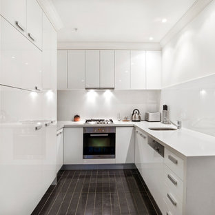 Design ideas for a contemporary u-shaped kitchen in Melbourne with an undermount sink, flat-panel cabinets, white cabinets, white splashback, stainless steel appliances and no island.