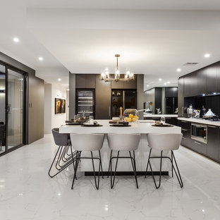 Design ideas for a contemporary l-shaped open plan kitchen in Perth with an undermount sink, flat-panel cabinets, black cabinets, black splashback, glass sheet splashback, black appliances, marble floors, with island and white floor.