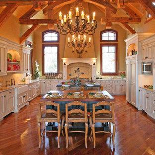 Geräumige Rustikale Wohnküche in U-Form mit Landhausspüle, profilierten Schrankfronten, weißen Schränken, Granit-Arbeitsplatte, Küchenrückwand in Beige, Rückwand aus Porzellanfliesen, Küchengeräten aus Edelstahl, braunem Holzboden und zwei Kücheninseln in Sonstige