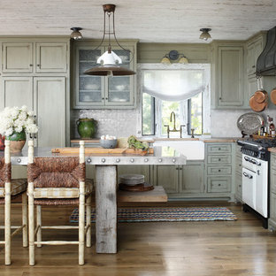 Inspiration for a country l-shaped kitchen in Milwaukee with a farmhouse sink, shaker cabinets, distressed cabinets, wood benchtops, grey splashback, mosaic tile splashback and panelled appliances.