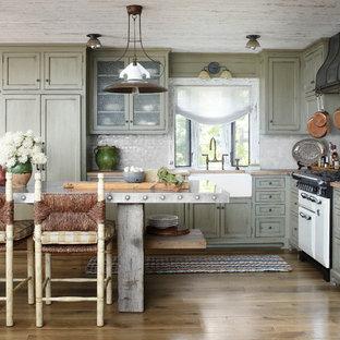 ミルウォーキーのラスティックスタイルのおしゃれなL型キッチン (エプロンフロントシンク、シェーカースタイル扉のキャビネット、ヴィンテージ仕上げキャビネット、木材カウンター、グレーのキッチンパネル、モザイクタイルのキッチンパネル、パネルと同色の調理設備) の写真