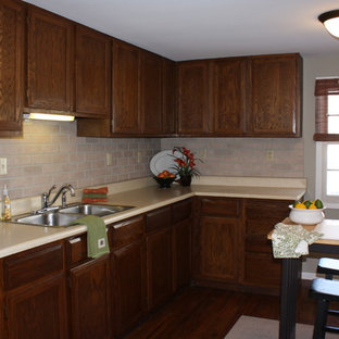 This is an example of a mid-sized traditional u-shaped separate kitchen in Milwaukee with a double-bowl sink, raised-panel cabinets, dark wood cabinets, laminate benchtops, pink splashback, brick splashback, white appliances, medium hardwood floors and with island.