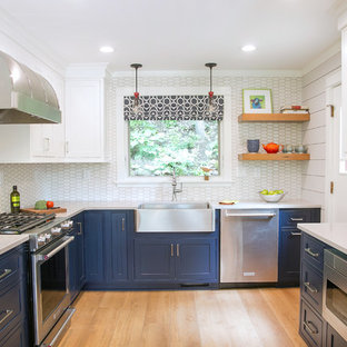 Small beach style u-shaped separate kitchen in Milwaukee with a farmhouse sink, recessed-panel cabinets, blue cabinets, quartz benchtops, white splashback, porcelain splashback, stainless steel appliances, light hardwood floors, beige benchtop and beige floor.
