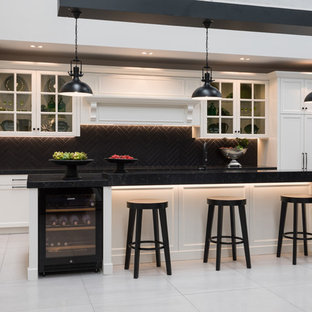 Design ideas for an expansive traditional eat-in kitchen in Auckland with a double-bowl sink, shaker cabinets, white cabinets, quartz benchtops, black splashback, subway tile splashback, stainless steel appliances, porcelain floors, with island, grey floor and black benchtop.