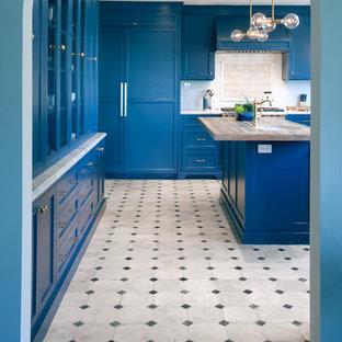 Große Mediterrane Küche in U-Form mit Schrankfronten mit vertiefter Füllung, blauen Schränken, Marmor-Arbeitsplatte, Küchenrückwand in Weiß, Rückwand aus Metrofliesen, Elektrogeräten mit Frontblende, Kücheninsel und buntem Boden in Los Angeles