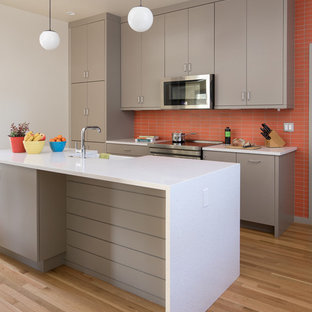 Mid-century modern kitchen pictures - 1960s galley light wood floor and beige floor kitchen photo in Portland with a farmhouse sink, flat-panel cabinets, gray cabinets, orange backsplash, stainless steel appliances, a peninsula and white countertops