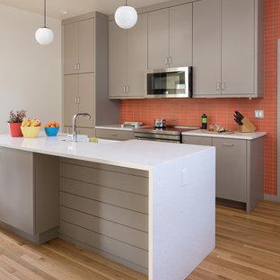 ポートランドのミッドセンチュリースタイルのおしゃれなキッチン (エプロンフロントシンク、フラットパネル扉のキャビネット、グレーのキャビネット、オレンジのキッチンパネル、シルバーの調理設備、淡色無垢フローリング、ベージュの床、白いキッチンカウンター) の写真