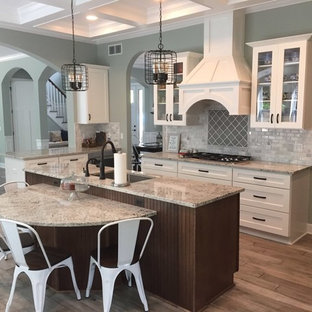 This is an example of a medium sized traditional galley kitchen/diner in Detroit with a single-bowl sink, recessed-panel cabinets, white cabinets, granite worktops, multi-coloured splashback, ceramic splashback, stainless steel appliances, plywood flooring, an island and grey floors.