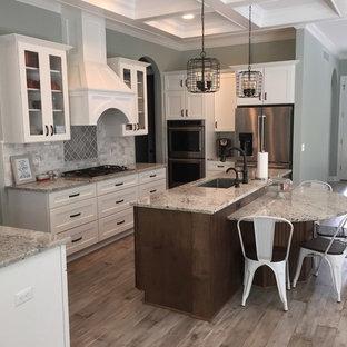 Zweizeilige, Mittelgroße Klassische Wohnküche mit Waschbecken, Schrankfronten mit vertiefter Füllung, weißen Schränken, Granit-Arbeitsplatte, bunter Rückwand, Rückwand aus Keramikfliesen, Küchengeräten aus Edelstahl, Sperrholzboden, Kücheninsel und grauem Boden in Detroit