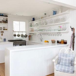 На фото: маленькая п-образная кухня в морском стиле с открытыми фасадами, белыми фасадами, паркетным полом среднего тона, полуостровом и техникой из нержавеющей стали