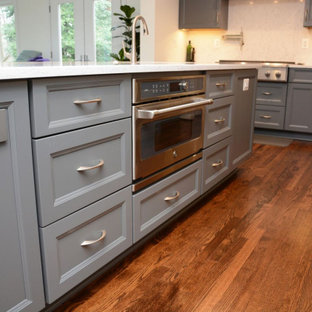 Large transitional open concept kitchen remodeling - Open concept kitchen - large transitional u-shaped medium tone wood floor open concept kitchen idea in DC Metro with an undermount sink, gray cabinets, quartz countertops, white backsplash, stainless steel appliances, an island and white countertops
