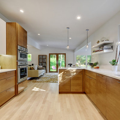 Inspiration for a large mid-century modern galley light wood floor eat-in kitchen remodel in Austin with an undermount sink, flat-panel cabinets, medium tone wood cabinets, quartz countertops, white backsplash, glass sheet backsplash and stainless steel appliances