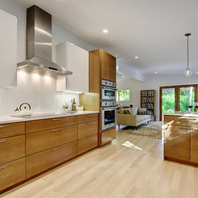 Eat-in kitchen - large 1960s galley light wood floor eat-in kitchen idea in Austin with an undermount sink, flat-panel cabinets, medium tone wood cabinets, quartz countertops, white backsplash, glass sheet backsplash and stainless steel appliances