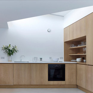 Medium sized contemporary l-shaped kitchen in London with a submerged sink, flat-panel cabinets, light wood cabinets, integrated appliances, grey floors and white worktops.
