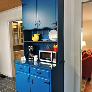 Small midcentury l-shaped separate kitchen in Other with a double-bowl sink, flat-panel cabinets, grey cabinets, solid surface benchtops, multi-coloured splashback, mosaic tile splashback, stainless steel appliances, slate floors, a peninsula, black floor and grey benchtop.