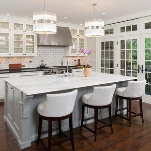 Idee per una grande cucina american style con lavello a doppia vasca, ante di vetro, ante bianche, top in marmo, paraspruzzi bianco, paraspruzzi con piastrelle diamantate, elettrodomestici in acciaio inossidabile, parquet scuro, isola e pavimento marrone