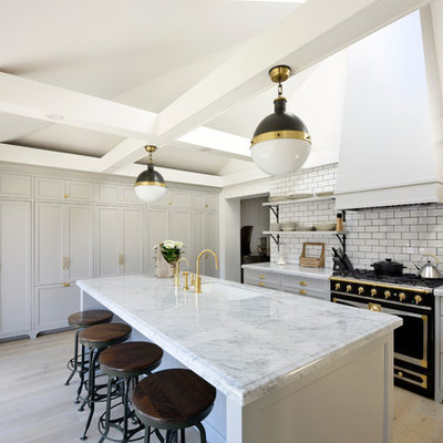 Transitional galley medium tone wood floor eat-in kitchen photo in Ottawa with recessed-panel cabinets, gray cabinets, marble countertops, white backsplash, subway tile backsplash, black appliances, an island and an undermount sink