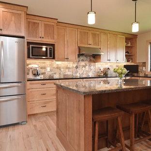 Modelo de cocina en L, tradicional, con armarios estilo shaker, puertas de armario de madera clara, salpicadero beige, electrodomésticos de acero inoxidable y salpicadero de pizarra