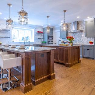 Geräumige, Offene Moderne Küche in L-Form mit Schrankfronten im Shaker-Stil, grauen Schränken, Quarzit-Arbeitsplatte, Küchenrückwand in Grau, Rückwand aus Steinfliesen, Küchengeräten aus Edelstahl, braunem Holzboden und zwei Kücheninseln in Boston
