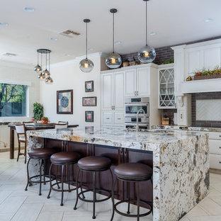 フェニックスのトランジショナルスタイルのおしゃれなキッチン (レイズドパネル扉のキャビネット、白いキャビネット、グレーのキッチンパネル、レンガのキッチンパネル、シルバーの調理設備、淡色無垢フローリング、白い床、マルチカラーのキッチンカウンター) の写真