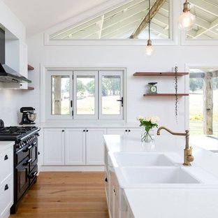 This is an example of a large traditional l-shaped open plan kitchen in Other with a farmhouse sink, recessed-panel cabinets, white cabinets, white splashback, ceramic splashback, black appliances, medium hardwood floors, multiple islands, brown floor, white benchtop and quartz benchtops.