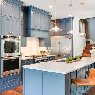 Ispirazione per una cucina a L tradizionale con lavello sottopiano, ante in stile shaker, ante blu, paraspruzzi bianco, elettrodomestici in acciaio inossidabile, pavimento in legno massello medio, isola, pavimento marrone e top bianco