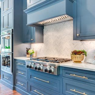 ダラスの広いトランジショナルスタイルのおしゃれなキッチン (アンダーカウンターシンク、シェーカースタイル扉のキャビネット、青いキャビネット、大理石カウンター、グレーのキッチンパネル、大理石のキッチンパネル、シルバーの調理設備、無垢フローリング、茶色い床、白いキッチンカウンター) の写真