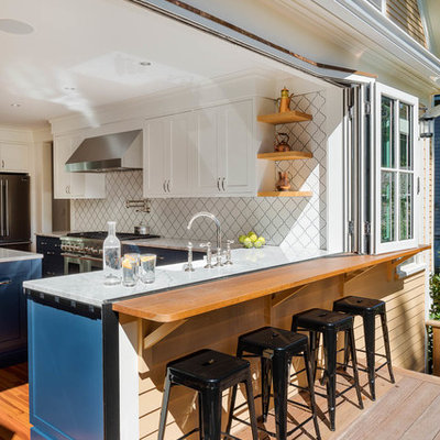 Mid-sized trendy l-shaped medium tone wood floor and brown floor eat-in kitchen photo in Boston with a farmhouse sink, recessed-panel cabinets, white cabinets, quartzite countertops, white backsplash, porcelain backsplash, stainless steel appliances and an island
