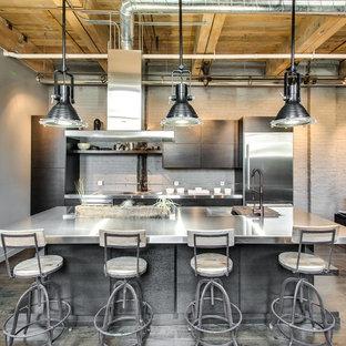 Inspiration pour une cuisine ouverte parallèle urbaine de taille moyenne avec un évier 2 bacs, un placard à porte plane, des portes de placard grises, un plan de travail en inox, une crédence grise, un électroménager en acier inoxydable, un sol en bois clair et un îlot central.