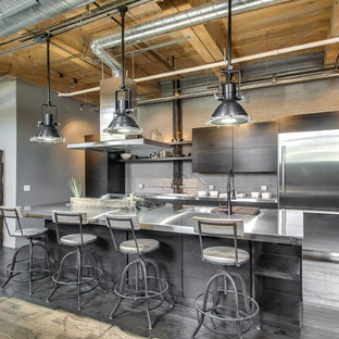 This is an example of a mid-sized industrial galley open plan kitchen in Chicago with a double-bowl sink, flat-panel cabinets, grey cabinets, stainless steel benchtops, grey splashback, stainless steel appliances, light hardwood floors and with island.