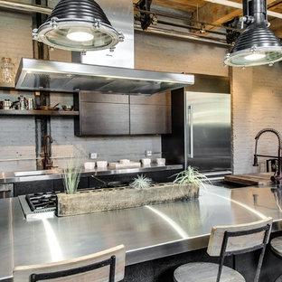 Offene, Zweizeilige, Mittelgroße Industrial Küche mit Doppelwaschbecken, flächenbündigen Schrankfronten, grauen Schränken, Edelstahl-Arbeitsplatte, Küchenrückwand in Grau, Küchengeräten aus Edelstahl, hellem Holzboden und Kücheninsel in Chicago