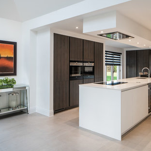 This is an example of a contemporary l-shaped kitchen/diner in Kent with a submerged sink, flat-panel cabinets, brown cabinets, black appliances, an island, beige floors and white worktops.