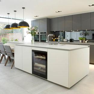 Diseño de cocina comedor lineal, actual, de tamaño medio, con fregadero bajoencimera, armarios con paneles lisos, puertas de armario blancas, salpicadero con efecto espejo, una isla y suelo gris