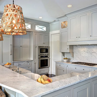 Mid-sized traditional kitchen ideas - Example of a mid-sized classic l-shaped dark wood floor and brown floor kitchen design in Charleston with a farmhouse sink, gray cabinets, white backsplash, paneled appliances, beaded inset cabinets, stone slab backsplash, an island and quartzite countertops