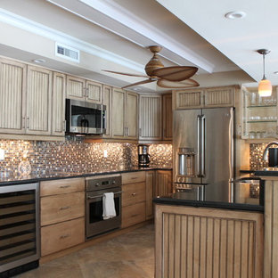 This is an example of a mid-sized tropical u-shaped eat-in kitchen in Miami with an undermount sink, medium wood cabinets, granite benchtops, multi-coloured splashback, glass tile splashback, stainless steel appliances, travertine floors, with island and louvered cabinets.