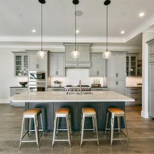 Foto di una cucina chic con lavello sottopiano, ante in stile shaker, ante grigie, paraspruzzi bianco, elettrodomestici da incasso, pavimento in legno massello medio, isola, pavimento marrone e top bianco