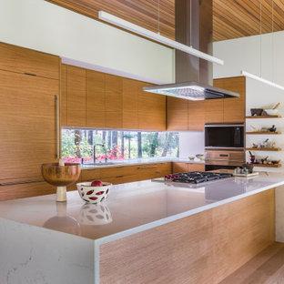 Foto på ett funkis vit kök, med en undermonterad diskho, släta luckor, skåp i ljust trä, bänkskiva i kvarts, rostfria vitvaror, ljust trägolv och en köksö