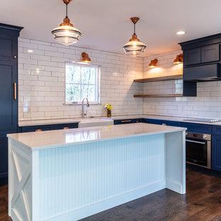 Geräumige Landhausstil Küche in L-Form mit Landhausspüle, Glasfronten, blauen Schränken, Quarzwerkstein-Arbeitsplatte, Küchenrückwand in Weiß, Rückwand aus Keramikfliesen, Küchengeräten aus Edelstahl, braunem Holzboden, Kücheninsel, braunem Boden und weißer Arbeitsplatte in St. Louis