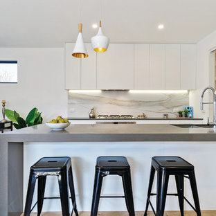 This is an example of a mid-sized contemporary galley open plan kitchen in Melbourne with an undermount sink, white cabinets, quartz benchtops, stainless steel appliances, light hardwood floors, with island, brown floor and grey benchtop.