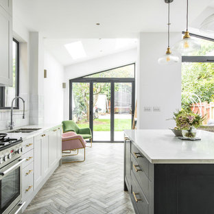 Photo of a traditional l-shaped kitchen in London with a double-bowl sink, shaker cabinets, white cabinets, white splashback, stainless steel appliances, medium hardwood flooring, an island, brown floors and white worktops.
