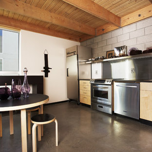 Mid-sized eclectic kitchen ideas - Kitchen - mid-sized eclectic single-wall concrete floor kitchen idea in Phoenix with stainless steel appliances, a drop-in sink, flat-panel cabinets, light wood cabinets, laminate countertops, gray backsplash and no island