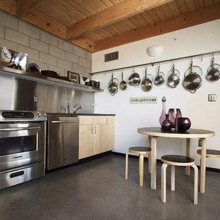 Ispirazione per una piccola cucina eclettica con elettrodomestici in acciaio inossidabile, ante lisce, ante in legno chiaro, paraspruzzi a effetto metallico, paraspruzzi con piastrelle di metallo, lavello da incasso, top in laminato, pavimento in cemento e nessuna isola