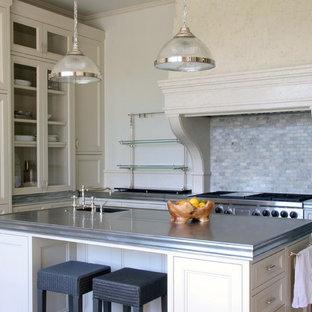 ロサンゼルスのトランジショナルスタイルのおしゃれなキッチン (ガラス扉のキャビネット、ベージュのキャビネット、亜鉛製カウンター、マルチカラーのキッチンパネル、石タイルのキッチンパネル、パネルと同色の調理設備) の写真