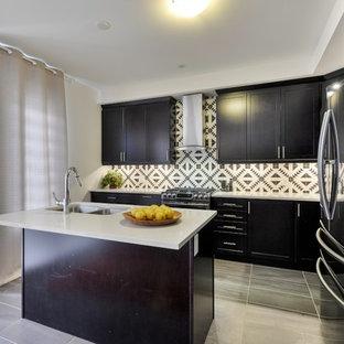 トロントの中サイズのエクレクティックスタイルのおしゃれなキッチン (ダブルシンク、シェーカースタイル扉のキャビネット、黒いキャビネット、珪岩カウンター、白いキッチンパネル、セメントタイルのキッチンパネル、黒い調理設備、磁器タイルの床、グレーの床) の写真