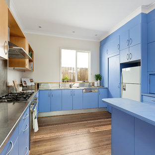 Mid-sized beach style u-shaped separate kitchen in Sydney with an integrated sink, flat-panel cabinets, blue cabinets, stainless steel benchtops, metallic splashback, metal splashback, white appliances, dark hardwood floors, a peninsula and brown floor.