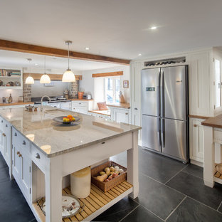 This is an example of a large country single-wall kitchen in Cornwall with an undermount sink, shaker cabinets, beige cabinets, concrete benchtops, grey splashback, ceramic splashback, stainless steel appliances, concrete floors, with island and black floor.
