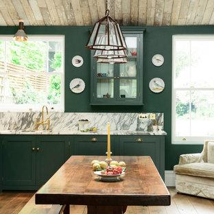 ロンドンの中くらいのトラディショナルスタイルのおしゃれなキッチン (ダブルシンク、シェーカースタイル扉のキャビネット、緑のキャビネット、大理石カウンター、石スラブのキッチンパネル、黒い調理設備、淡色無垢フローリング、アイランドなし) の写真