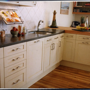 Inspiration for a mid-sized traditional galley kitchen in Auckland with a single-bowl sink, recessed-panel cabinets, white cabinets, concrete benchtops, white splashback, ceramic splashback, panelled appliances, medium hardwood floors, multiple islands, orange floor and grey benchtop.